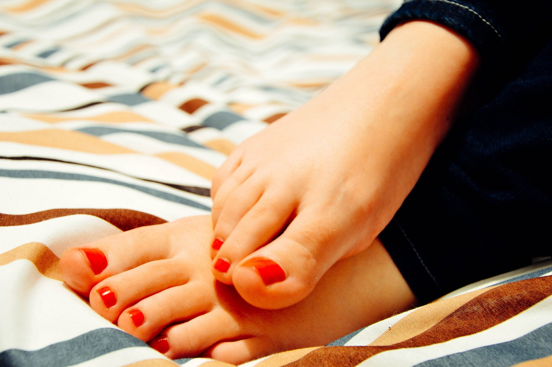 Close up of a woman's pedicured toes with red nail polish. Serving as a featured image for the Pedicure Course featured image.