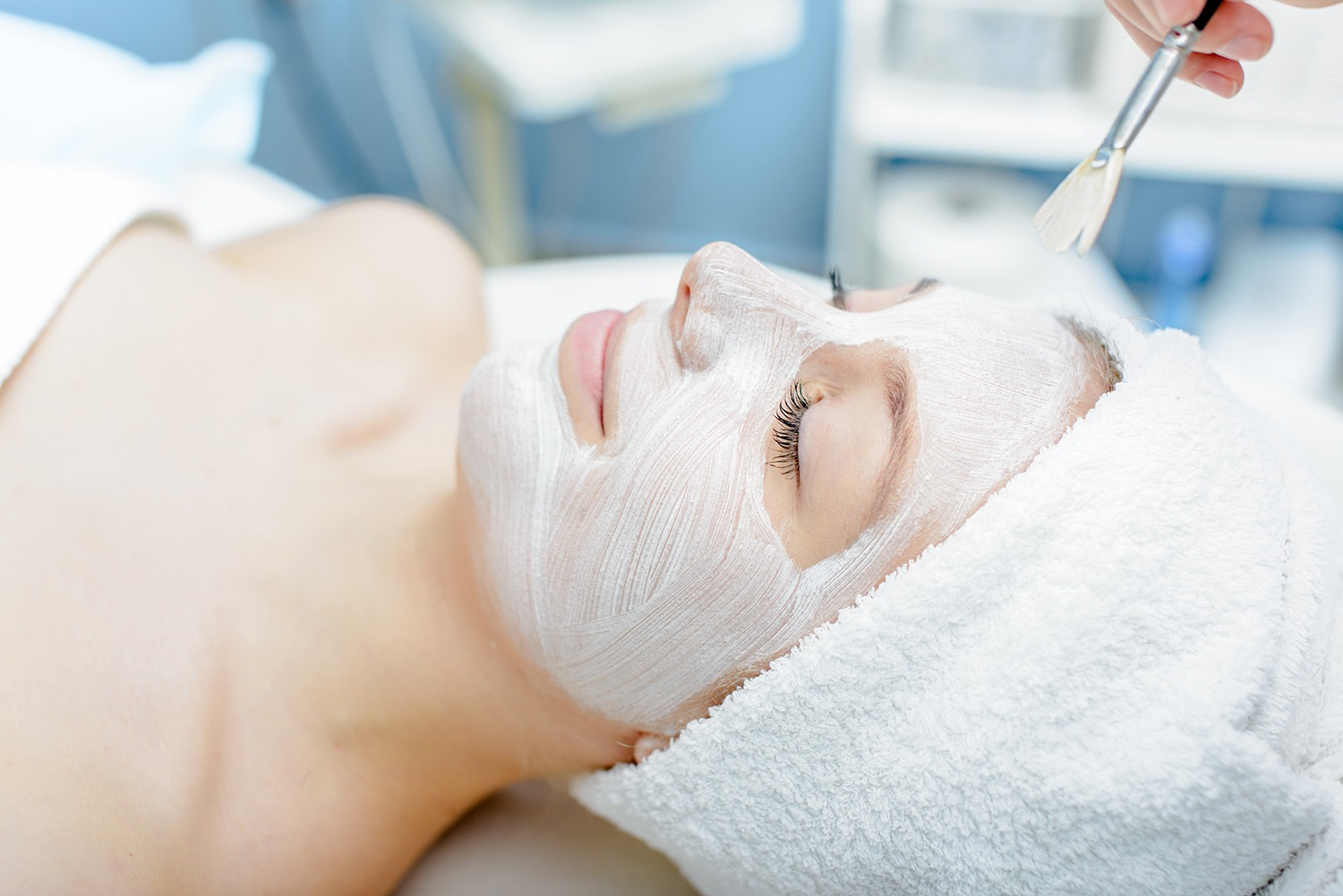 Woman lay down with her eyes closed while being given a facial skin care treatment. For the use on the Facials Course Page.