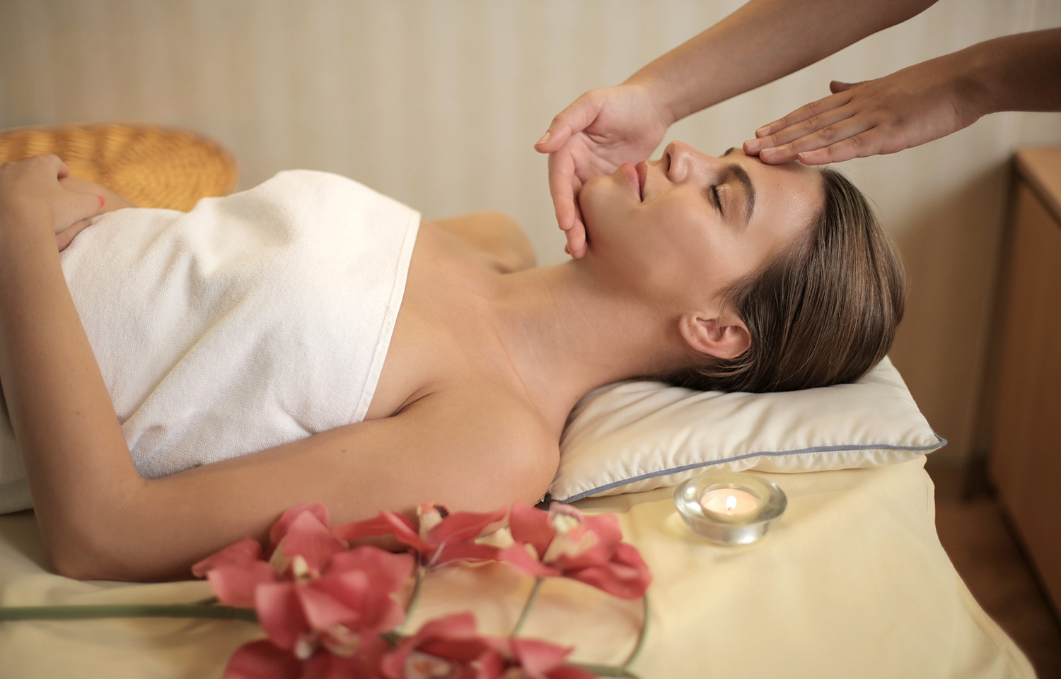 Woman lay down on a massage table having a beauty therapy treatment applied to her. For use on the Level 3 Beauty Therapy Course page.