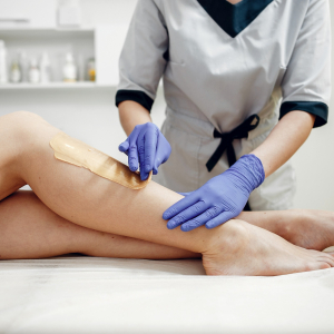 Woman's legs being waxed by a beautician in a salon. For use on the Waxing Course page.