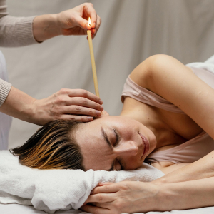 A woman lay down on her side with a beautican applying an ear candling treatment to her. For use of the Ear Candling Course page.