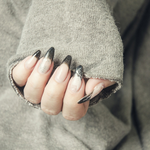 Close up of a woman wearing a baggy jumper, waring long acrylic nails with black glittery tips. For use on the Acrylic Nails Course Page.