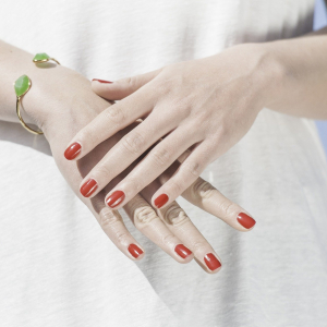 Close up of a woman's manicured hands and red painted nails. For the use of Manicure course page.