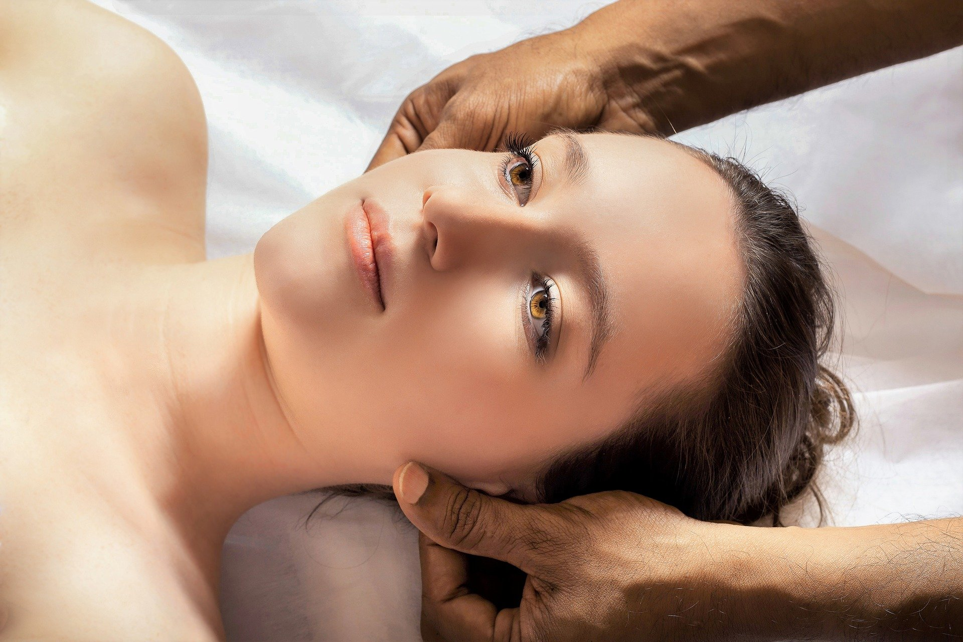 Woman lay on her back while a man carries out an Indian head massage on her. For use on the Indian Head Massage Course page.