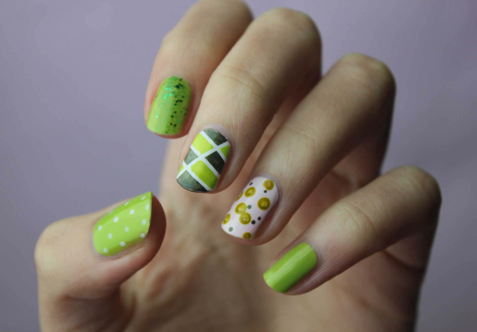 Close up of green themed nail art on a woman's hand. For use on the Basic Nail Art Course page.