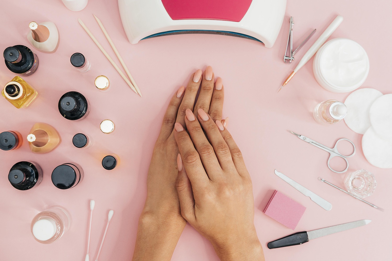 Close up of a woman's hands on a pink desk, surrounded by nail equipment and products. For use on Level 3 Nail Technology Course Page.