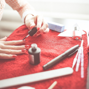 Close up of a beauty table displaying various nail technician equipment. A woman is applying gel nail polish to her hands. For use on the Gel Polish Course Page.