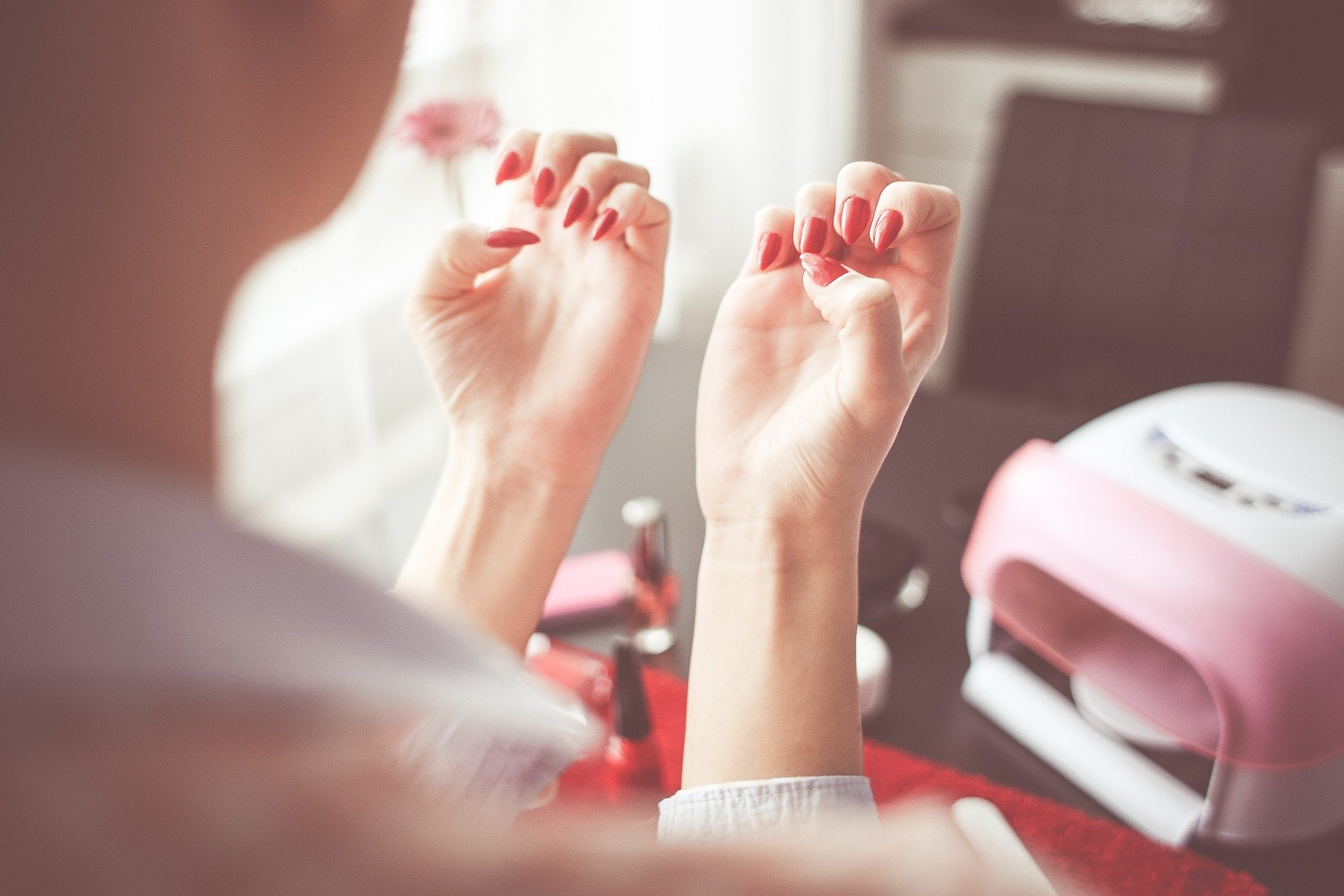 woman showing off her red gel nails in a beauty, nail salon. For use on the Gel Nails Course page.