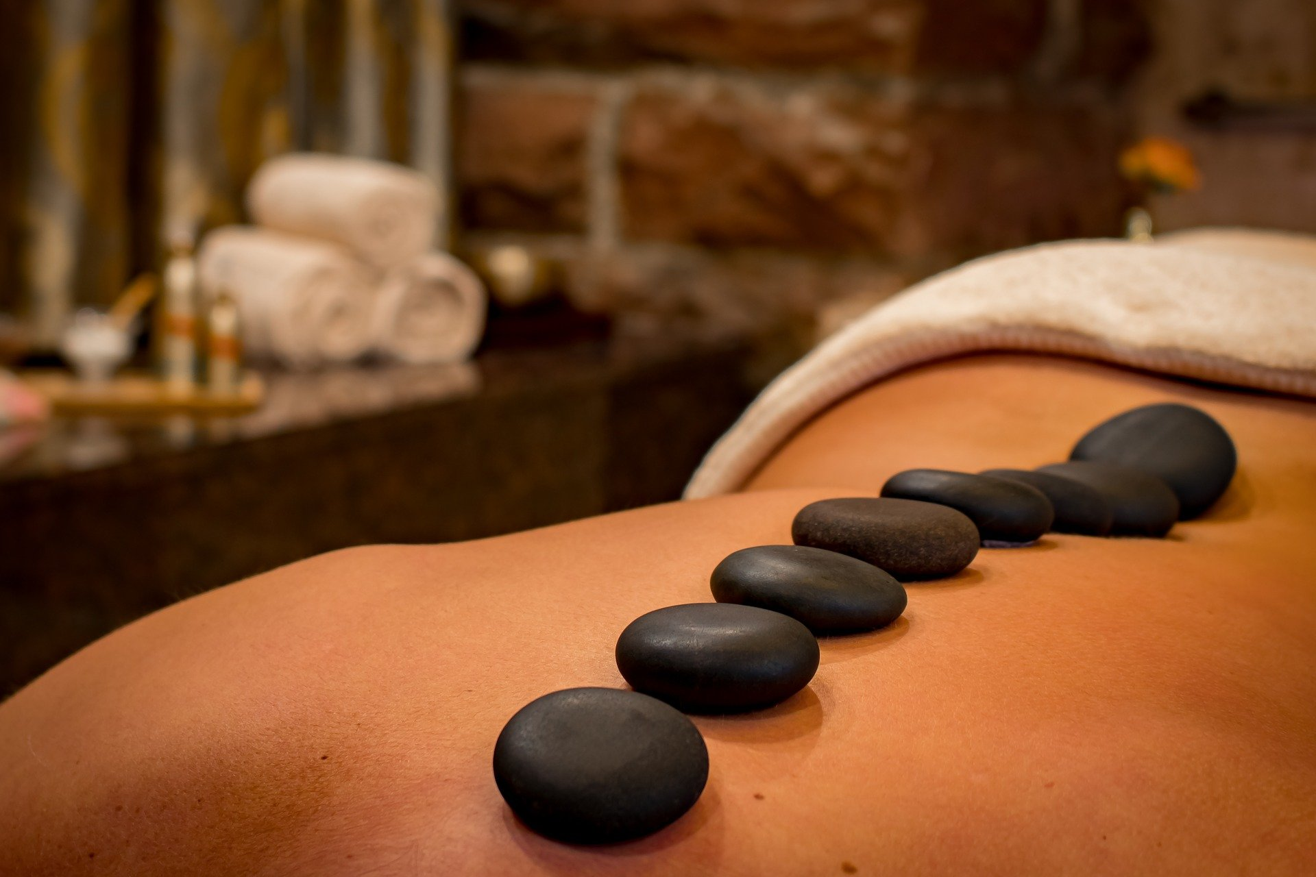 Close up of a woman's back with hot stones applied across her spine. For use on Hot Stone Therapy Course page.